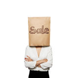 Woman under paper bag with sale written Stock Images