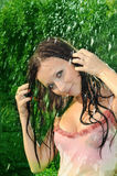 Woman under a rain. The young nice woman relaxing under a summer rain Stock Photos