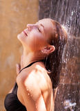 Woman under refreshing cold shower. Woman under refreshing shower, enjoying cold water drops after beach, closing eyes of pleasure, summer vacation Royalty Free Stock Image