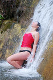 Woman under running water of waterfall. Royalty Free Stock Image