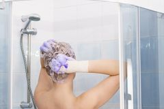 Woman under the shower with colored foam on hair royalty free stock images