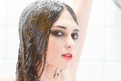Woman under shower. Young sensual woman under shower splash of water looking at camera Stock Photos