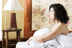 Woman under soft cover look to side Stock Photos