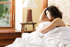 Woman under soft cover scratching her head Royalty Free Stock Photography
