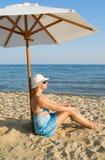 Woman under a solar umbrella. The woman under a solar umbrella on a beach stock images