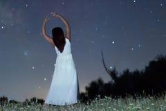 Woman under starry night in white long dress ballet pose raising arms Woman under night sky. Woman under starry night in white long dress ballet pose raising Stock Photo