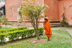 Woman under tree in Assam. Dibrugarh, Assam - circa March 2012: Native woman in orange clothes and with brown turban on her head stands in garden next to tree Stock Images