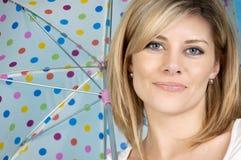 Woman under umbrella. An attractive woman under a polka dot umbrella Royalty Free Stock Photos