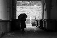 Woman under an umbrella in a dark arch royalty free stock photography
