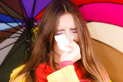Woman under umbrella sneezing in tissue Royalty Free Stock Images