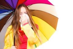 Woman under umbrella sneezing in tissue Royalty Free Stock Photo