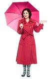 Woman under umbrella trying to feel rain Stock Image