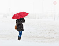 Woman walking in the winter city. Woman under an umbrella walking on a snow-covered town stock image