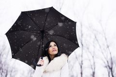 Woman under umrella while snowing Stock Photography