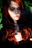 Woman under veil. Red hair young woman with black veil over face, outdoor shot Royalty Free Stock Image