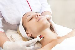 Woman undergoes the procedure of medical micro needle therapy with a modern medical instrument derma roller Stock Images