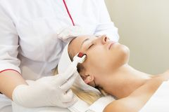 Woman undergoes the procedure of medical micro needle therapy with a modern medical instrument derma roller. Royalty Free Stock Photo