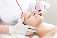 The woman undergoes the procedure of medical micro needle therapy. The women undergoes the procedure of medical micro needle therapy with a modern medical Royalty Free Stock Images
