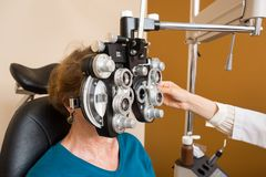 Woman Undergoing Eye Examination With Phoropter Stock Photo