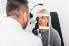 Woman undergoing eyesight exam in optician`s office. Ophthalmology, vision examination and treatment royalty free stock photos