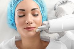 Woman undergoing laser tattoo removal procedure in salon. Closeup royalty free stock photo