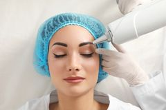 Woman undergoing laser tattoo removal procedure in salon. Closeup stock image
