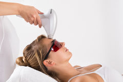 Woman Undergoing Laser Treatment At Salon Royalty Free Stock Images