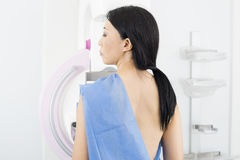 Woman Undergoing Mammogram X-ray Test. Rear view of mature woman undergoing mammogram X-ray test in hospital Stock Photos