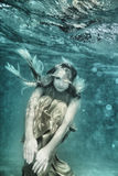 Woman underwater. Young beautiful woman in golden dress underwater Royalty Free Stock Photo