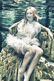 Woman underwater. Young beautiful woman in white dress underwater Stock Images