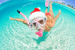 Woman Underwater christmas. Beautiful woman underwater with snorkel and christmas hat on vacation Stock Photo