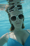 Woman underwater in pool. A woman underwater in a swimming pool wearing white sunglasses and a bathing suit Royalty Free Stock Photos