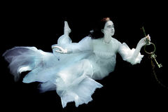 Woman Underwater Wearing White Gown. Floating Woman Underwater Wearing White Gown Royalty Free Stock Image