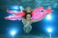 Woman underwater. Young woman underwater in the pool floating with pink foulard Stock Image