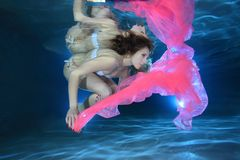 Woman underwater. Young woman underwater in the pool floating with pink foulard Royalty Free Stock Photo