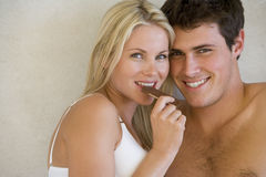 Woman in underwear eating chocolate by bare chested man, smiling, portrait Stock Images