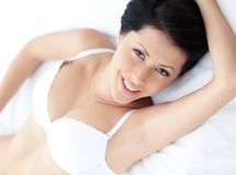 Woman in underwear is lying in the bed Stock Photography