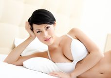 Woman in underwear is lying in the double bed Stock Image