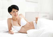 Woman in underwear is lying in the wonderful bed Stock Image