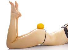 Woman in underwear with an orange on her buttock. Stock Photo