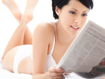 Woman in underwear reads newspaper Royalty Free Stock Images