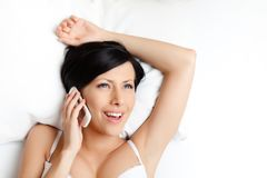Woman in underwear speaks on telephone Stock Images