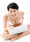 Woman in underwear is working on the thin computer Royalty Free Stock Photos