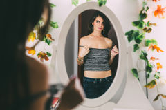 Woman undressing. Beautiful brunette woman looking in the mirror while taking off her shirt Royalty Free Stock Photos