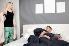 Woman undressing for bed. Woman standing at the side of the bed undressing and removing her dressing gown to join her husband under the bedclothes Royalty Free Stock Photos