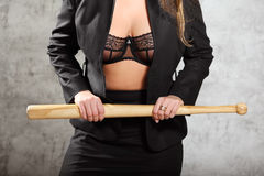 Woman in unfastened suit in bra hold bat Stock Images