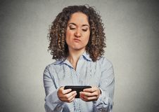 Woman unhappy, annoyed by someone on her cell phone while texting stock images