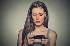 Woman unhappy, annoyed by something, someone on her cell phone texting Royalty Free Stock Photos