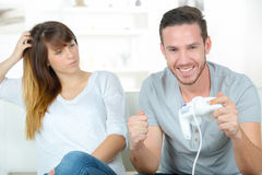 Woman unhappy with husband playing video-games. Woman unhappy with her husband playing video-games royalty free stock image