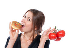 Woman unhealthy donut and  red tomatoes Royalty Free Stock Photo